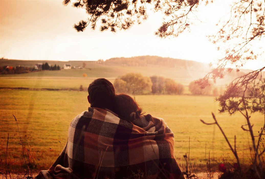 Man and woman hugging side by side wrapped in blanket